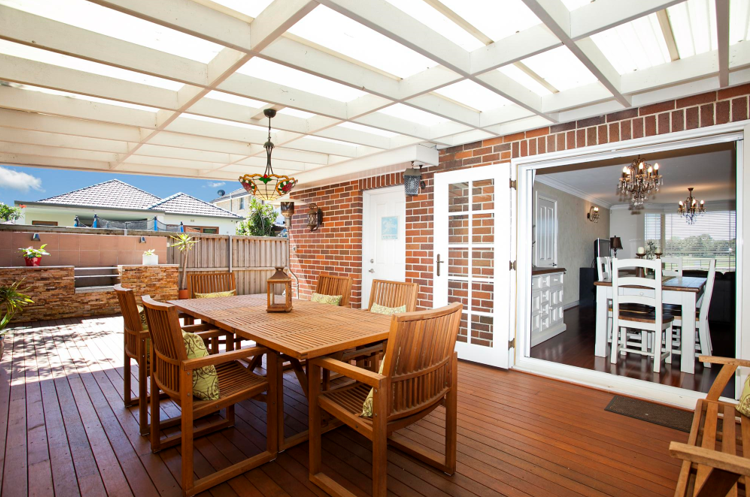 patio with roof, wooden floor and brick wall